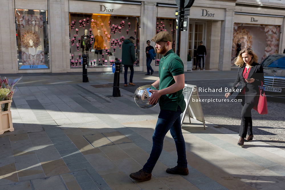 A florist working from a nearby kiosk carries a spherical container for bouquets after emptying stale water into a drain near the temporary renovation hoarding of luxury brand Louis Vuitton in New Bond Street, on 25th February 2019, in London, England.