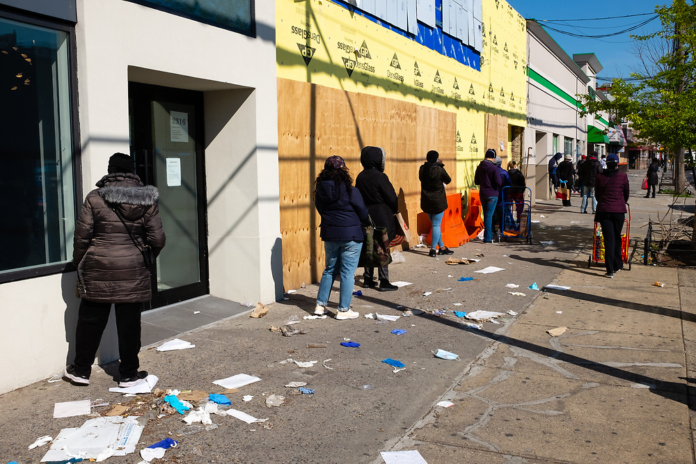 Brooklyn, NY - 17 April 2020. Patrons form a line amidst a drift of discarded surgical gloves and other trash outside a Dollar Tree store—with the green awning in the distance—on Nostrand Avenue in Brooklyn's Midwood neighborhood. The store sells frozen, canned, and packaged foods and is allowed to stay open during the stay-at-home orders.
