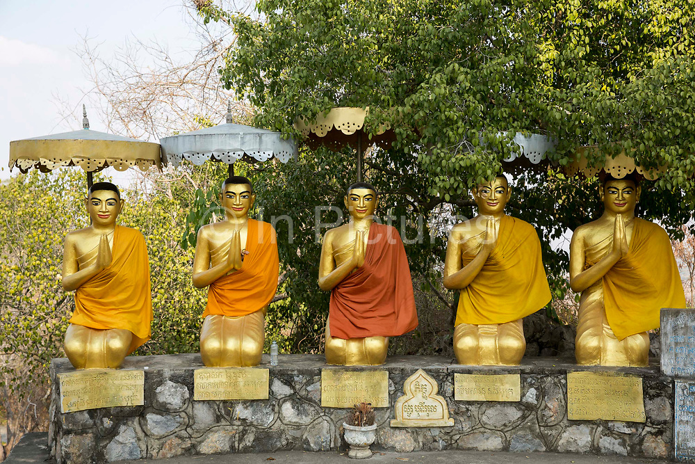 Five golden Buddhist statues covered with traditional orange robes in Vajrasana kneeling meditation position on a wall covered with traditional orange robes in Wat Banan, Battambang region, Cambodia, South East Asia.