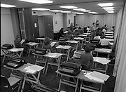 Conference Room at the EEC Building.   (N60)..1981..07.02.1981..02.07.1981..7th February 1981...At the EEC offices, 39 Molesworth Street, the conference room was converted to an examination hall for the purpose of recruiting staff..Image shows the room laid out with secretarial equipment as the applicants take their places for the exam.This invigilator answers a query from an applicant.