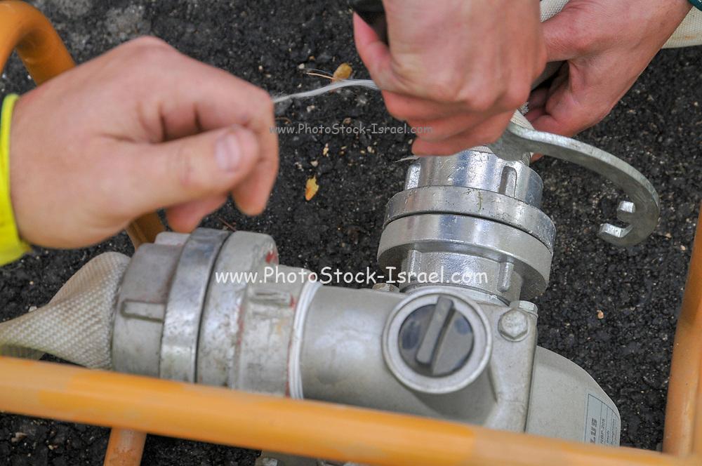 Firemen connect a fire house to a pump