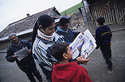 Slovak Roma, reading a Roma newspaper, living in all sorts of makeshift homes from old railway carriages to squats made from materials found in the rubbish dumps next to the cities. Slivinia, Slovakia.
