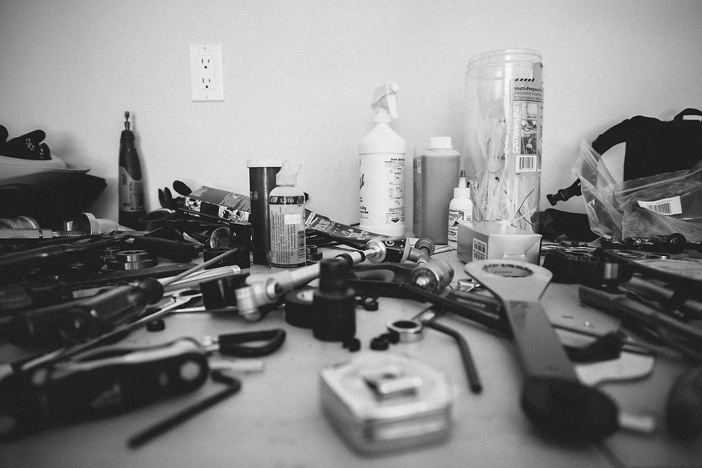Jay Goodrich's work bench covered with tools while he is in the process of building multiple bicycles in his garage.