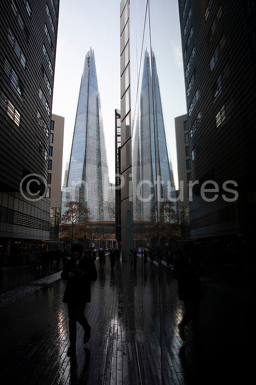 People in More London with The Shard looming behind on 27th November 2019 in London, England, United Kingdom. More London, part of an area known as London Bridge City, is a development on the south bank of the Thames. It is owned by the Kuwaiti sovereign wealth fund. It includes office blocks, shops, restaurants, cafes, and a pedestrianised area.