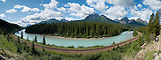 The railroad follows a U-shaped bend in Bow River at Morant's Curve, along Bow Valley Parkway, Highway 1A, in Banff National Park, ..Alberta, Canada. The Bow Range is part of the Canadian Rocky Mountains. Nicholas Morant (namesake for Morant's Curve) photographed the Rockies extensively in the 1930s and 1940s for Canadian Pacific Railway. This is part of the big Canadian Rocky Mountain Parks World Heritage Site declared by UNESCO in 1984. Panorama stitched from 8 images.