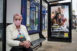 © Licensed to London News Pictures. 25/02/2021. WATFORD, UK.  A woman at a bus stop next to the UK Government's latest Covid-19 ad campaign which has been unveiled on digital screens in the town centre in Watford, Hertfordshire. The national ad campaign urges the public to continue with mask wearing, social distancing and hand washing.  England's stay at home order will remain in place until at least 29 March despite the minor easing of restrictions and the return of schools on 8 March.  Photo credit: Stephen Chung/LNP