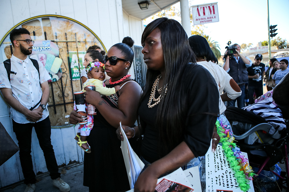 """Chemika Hollis, 25, holds her 3-month-old daughter Kai'lei as they arrive at a vigil held for her boyfriend Nathaniel Wilks, 24, in Oakland, Calif., Friday, August 14, 2015. Wilks was fatally shot by Oakland police officers on August 12.<br /> <br /> Wilks collided into another vehicle after leading police on an eight-mile-long pursuit, and then attempted a carjacking before being shot by three Oakland police officers in a foot pursuit. He was yielding a loaded 9-millimeter semiautomatic handgun at the time of the shooting less than a block away from the intersection of Martin Luther King Jr. Way and 27th Street, according to police. The gun had been reported stolen, but was never fired, said police authorities. Wilks was later pronounced dead at Highland Hospital in Oakland, California.<br /> <br /> Officer Johnna Watson, a spokeswoman for the Oakland Police Department, said that a preliminary autopsy report revealed that """"the bullets entered the front of the man's body."""" Witnesses claim that the suspect had stopped running and said, """"OK, OK, OK"""" indicating that he surrendered before being shot by police."""