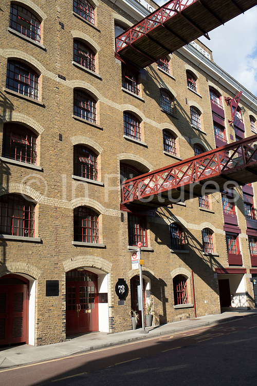 Gantry across the road at a wharf building on Wapping High Street in the East End of London, England, United Kingdom. These were once working wharf buildings, which are now residential apartments.