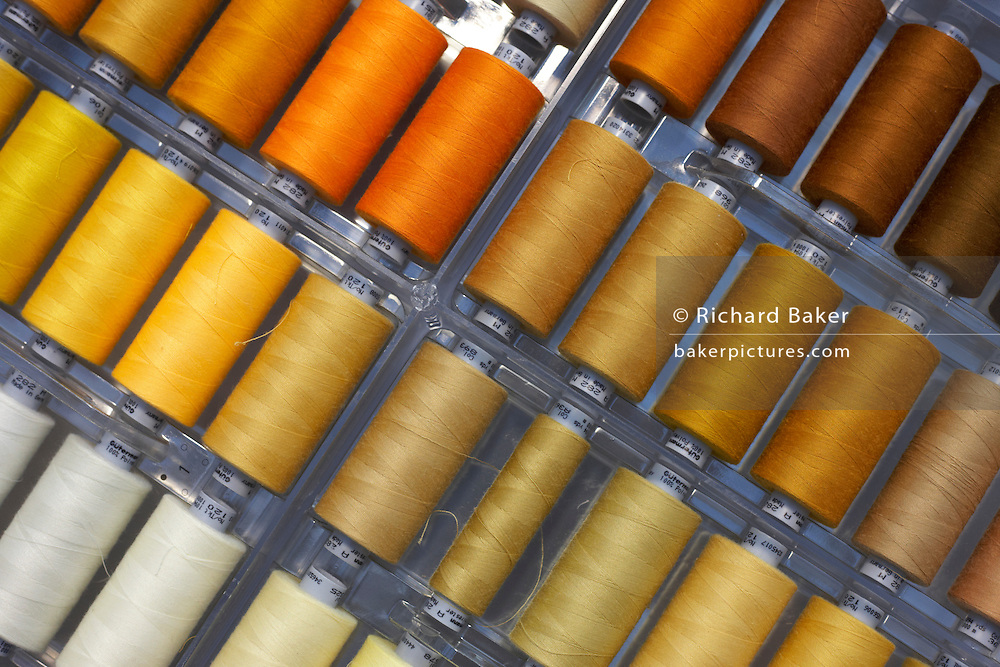"Shades of yellow and brown coloured cotton threads are seen in an open drawer used by couturier Margaret Howell is displayed in the company's workshop in Edmonton, North London. England. They lies diagonally, as flat neighbouring tones and ready for use in the many fine garments manufactured in this small factory. Howell is one of Britain's more understated of couture brands alongside more flamboyant personalities. Howell admits to being ""inspired by the methods by which something is made .. enjoying the tactile quality of natural fabrics such as tweeds, linen and cotton in a relaxed, natural and lived in look."""