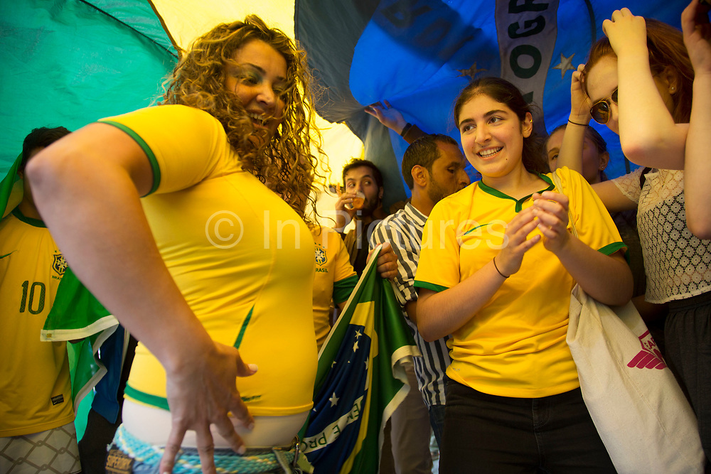 London, UK. Thursday 12th June 2014. Dancing and singing in joy underneath a giant Brazilian flag. Brazilians gather for the Brazil Day celebrations in Trafalgar Sq. A gathering to celebrate the beginning of the Brazil 2014 FIFA World Cup. Revellers sing and dance and play football games and all in the yellow green and blue of the Brazilian flag.
