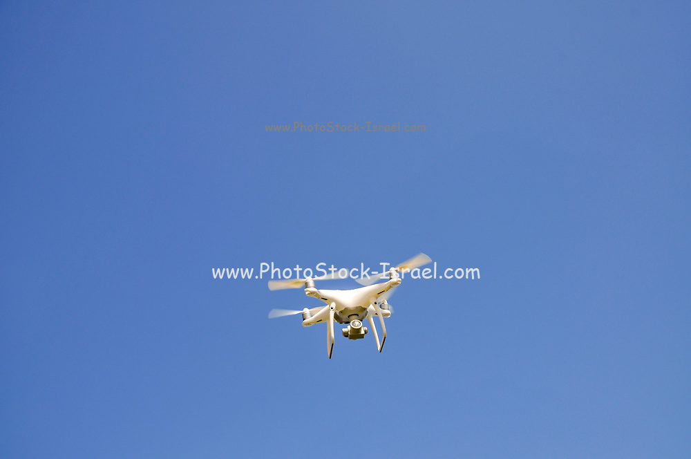 Remote control Quadrocopter, drone, with camera flying against a blue sky