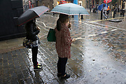 London, UK. Sunday 23rd August 2015. Heavy summer rain showers in the West End. People brave the wet weather armed with umbrellas and waterproof clothing. Covent Garden.