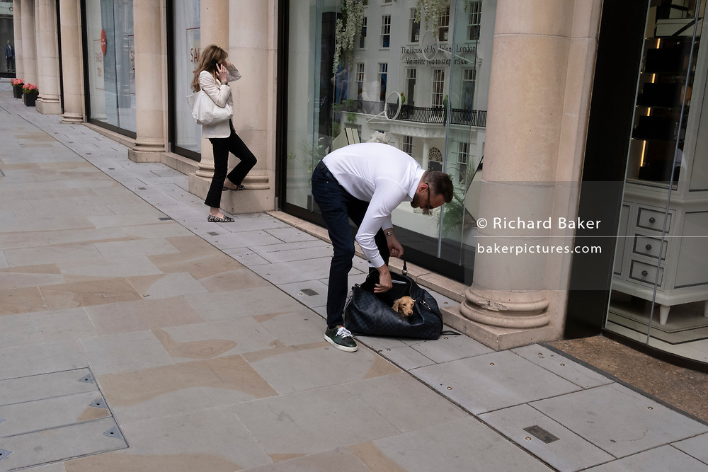 A dog owner folds his spaniel into a shoulder bag for safety on New Bond Street, on 12th July 2021, in London, England.