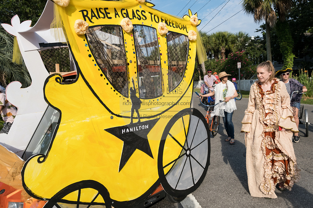 Women wearing colonial costume walk alongside a golf cart decorated as a horse carriage during the annual Independence Day parade July 4, 2019 in Sullivan's Island, South Carolina. The tiny affluent Sea Island beach community across from Charleston holds an outsized golf cart parade featuring more than 75 decorated carts.