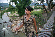Nepal is a moutainous country with deep valleys and rivers. A young woman is crossing a steel hanging bridge, called a monkey bridge in Dhading.