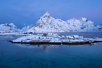 Olstind mountain peak rises over Sakrisøy island and yellow rorbu cabins, Moskenesøy, Lofoten Islands, Norway