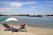 Nederland, Ooijpolder, 12-8-2020 Mensen zoeken verkoeling langs het water op deze tropische dag. Langs de rivieren zoals hier aan de Waal, rijn, zijn veel rivierstrandjes waar mensen gebruik van maken. Foto: ANP/ Hollandse Hoogte/ Flip Franssen