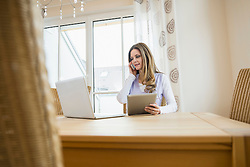 Woman with laptop, digital tablet and smartphone at home
