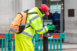 © Licensed to London News Pictures. 12/10/2020. London, UK. A worker disinfects a predestrian crossing button in Oxford Street, London as a Westminster cleaner disinfects a pedestrian crossing. Prime Minister Boris Johnson will announce in a statement to the Commons today a new three tier lockdown system before a televised address to the Nation tonight over the increasing levels of coronavirus infections in the UK. Photo credit: Alex Lentati/LNP