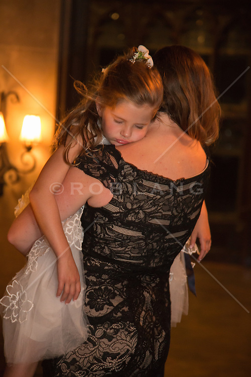 little girl in a formal dress asleep in the arms of a woman