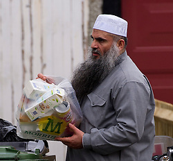 © London News Pictures. 08/01/2013. London, UK. Radical Preacher Abu Qatada taking out the rubbish at his bail home in London on January 8, 2013. Qatada was recently moved to the new property after Qatada and his family asked to be relocated. Photo Credit: Ben Cawthra/LNP