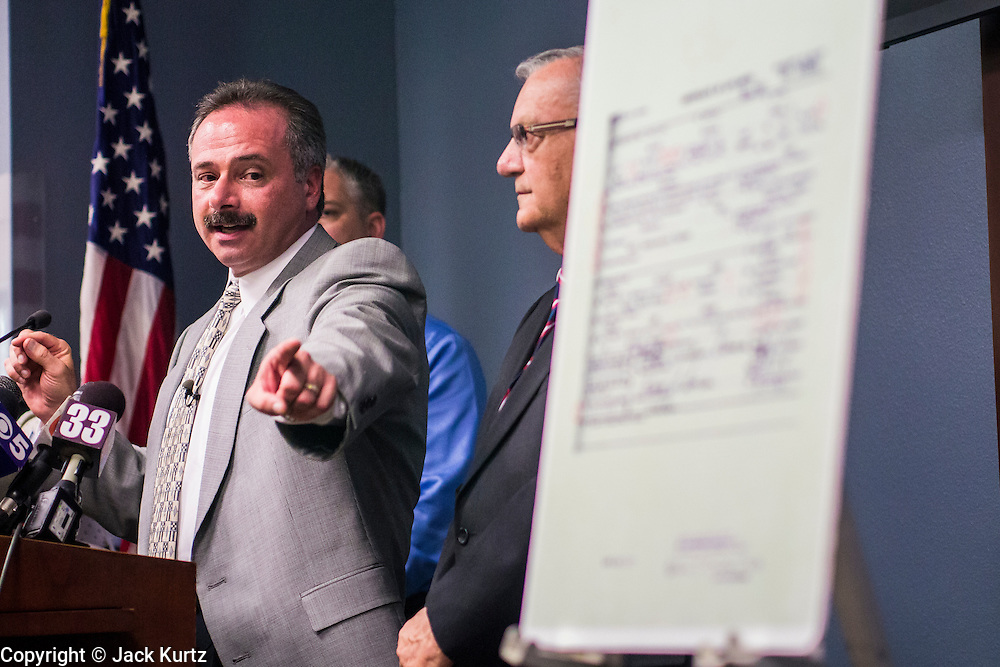 17 JULY 2012 - PHOENIX, AZ: MIKE ZULLO (left), the Sheriff's volunteer investigator, at the announcement that President Obama's birth certificate is not authentic, points to a copy of the birth certificate. Zullo said his investigation proves that the long form birth certificate President Barrack Obama has used to prove his citizenship is a fraud. He also said that Hawaii's lax standards for getting a birth certificate may pose a serious flaw to the United States' national security. PHOTO BY JACK KURTZ