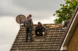 Two builders work closely to fit a Velux window.  <br />
