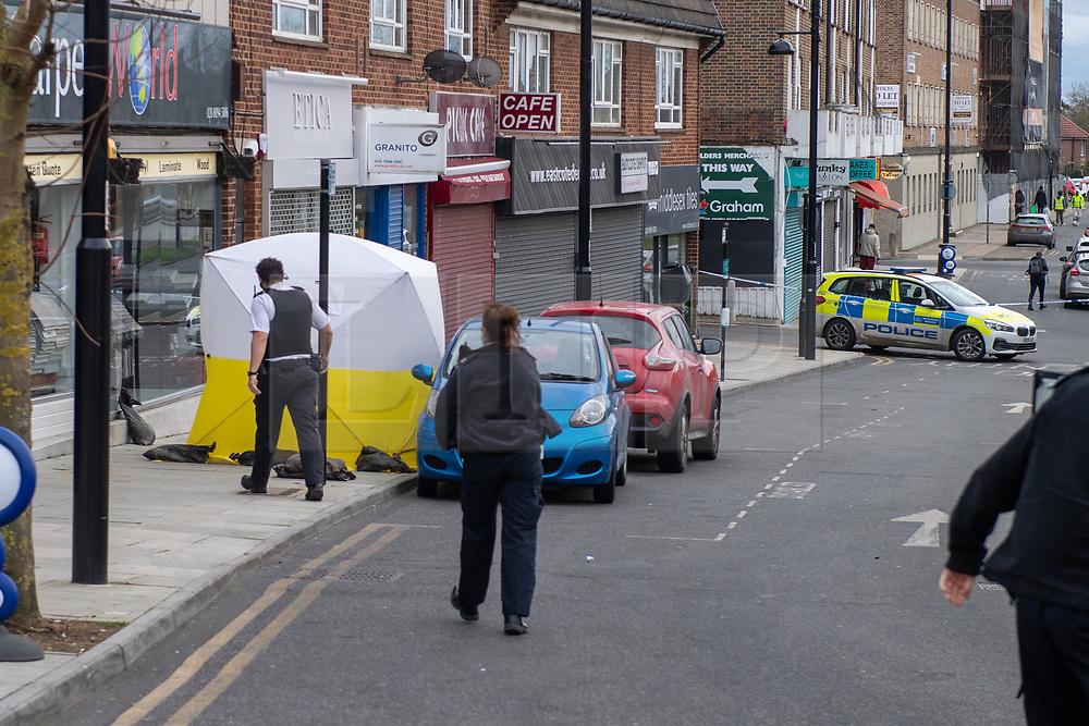© Licensed to London News Pictures. 11/01/2021. London, UK. Police officers walk toward a forensic tent at a block of shops on Field End Road where a man believed to be aged in his 40s died in suspicious circumstances. Metropolitan Police were called by London Ambulance Service shortly after 22:30GMT on Sunday, 10 January, following reports of a fight on Field End Road, Pinner. Officers attended, along with LAS, and found an unresponsive man. Despite the best efforts of emergency services, the man, believed to be aged in his 40s, was pronounced dead at the scene. The death is being treated as suspicious. A 21-year-old man was arrested in connection with the incident. Photo credit: Peter Manning/LNP