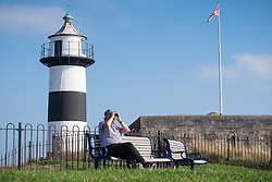 © Licensed to London News Pictures. 21/09/2016. Portsmouth, UK.  A man looking out to sea using binoculars by Southsea Castle in the warm and sunny afternoon in Southsea today, 21st September 2016. Photo credit: Rob Arnold/LNP
