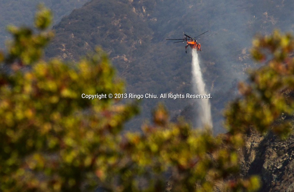 A helicopter makes a drop on a wildfire in the San Gabriel Mountains in Asuza, California., Tuesday, September. 24, 2013. The fire grew to 250 acres and was mostly burning in the Angeles National Forest, away from populated areas. It was 30 percent contained.  (Photo by Ringo Chiu/PHOTOFORMULA.com)