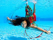 A 12 year old female teen dressed in colourful dress free diving underwater in a swimming pool. Model release available