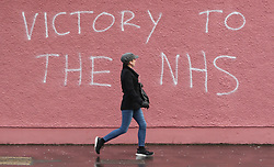 A woman walks past graffiti in support of NHS workers, on a wall of the Royal Victoria Hospital in Belfast.