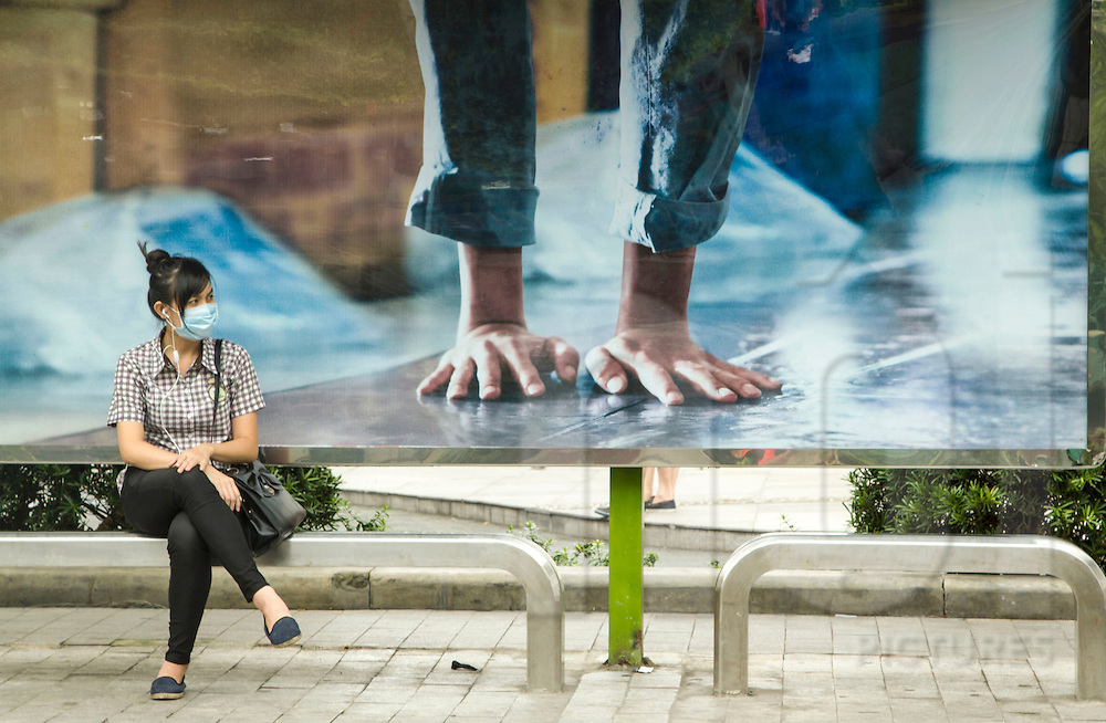Young woman waits on a bench at a bus stop in Cholon, Ho Chi Minh City, Vietnam, Southeast Asia. Behind her is a large billboard on which hands touch the ground as if in a handstand position.