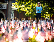 Aida Garcia, a UK student, paused to watch as  members of the UK  Army and Air Force ROTC held vigil for the victims of 9/11 reading the names of the victims among the flags in the front lawn of the Administration building  on Tuesday September 11, 2012 in Lexington, Ky.  Photo by Mark Cornelison   Staff
