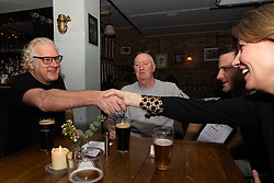 Dedicated Remainer musician and producer Paul Greendale, 54, and remainer Samantha Dark shake hands as they are introduced at the Whippet Inn in Kensal Rise, North West London, watched by Brexiteer Philip Davenport, 63, a construction worker, ahead of a discussion on Brexit with Bild Reporter Philip Fabian in London. London January 13 2019.