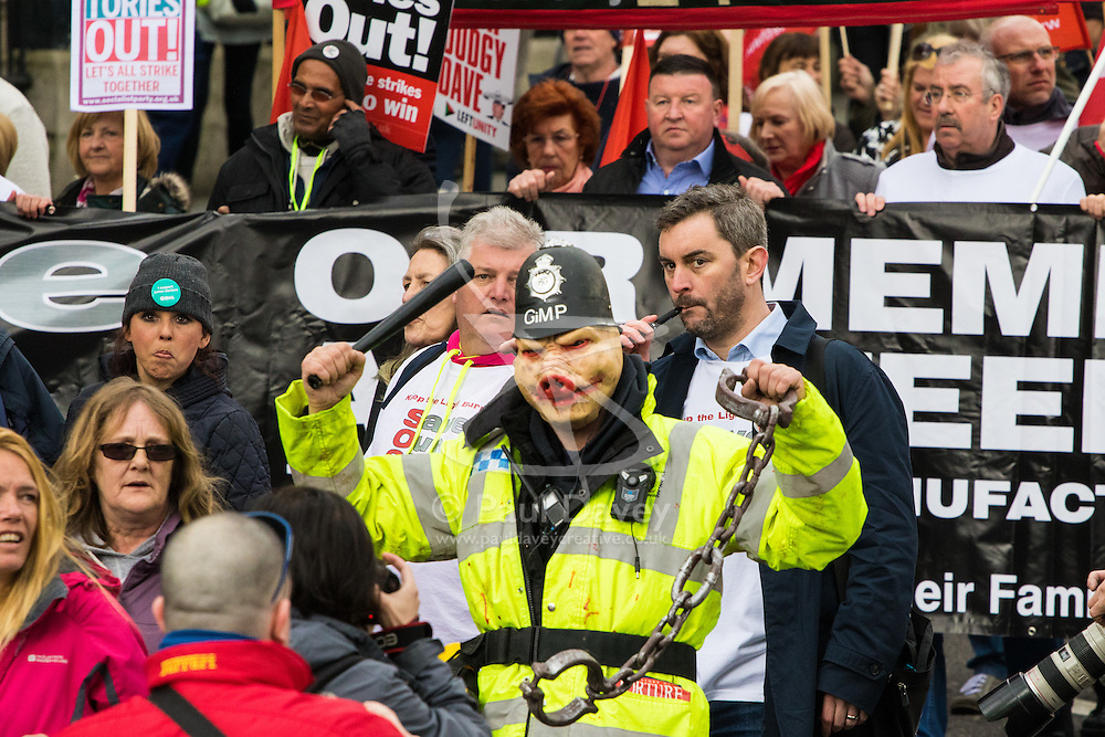 """London, April 16th 2016. A """"policeman"""" wears a pig mask as thousands of people supported by trade unions and other rights organisations demonstrate against the policies of the Tory government, including austerity and perceived favouring of """"the rich"""" over """"the poor""""."""