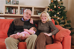 Family group with grandparents sitting together on sofa in living room holding grandson and smiling,