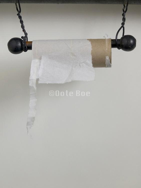 empty toilet paper roll on improvised holder