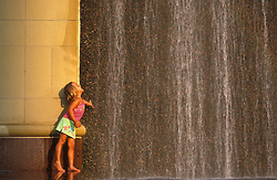 Stock photo of a young girl playing in a fountain