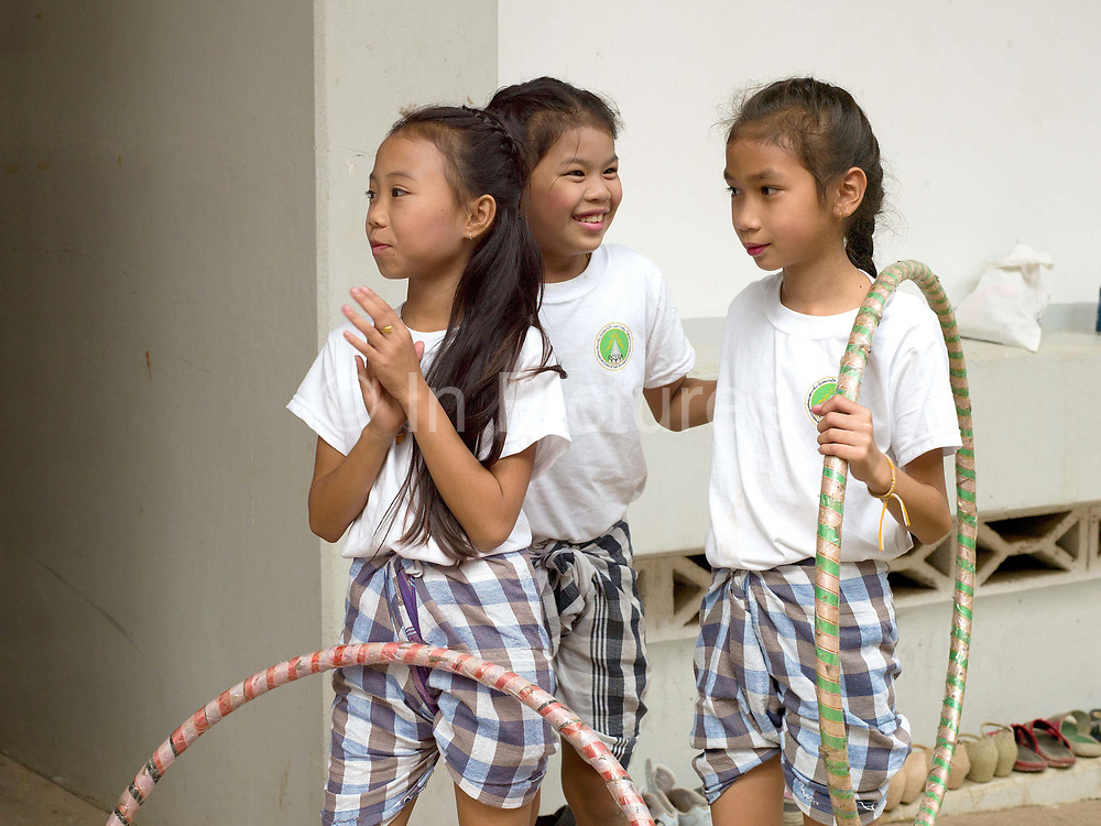 Three young Laotian girls wait behind the scenes before their hula hoop performance, Women's International Group (WIG) bazaar, Vientiane, Lao PDR. The WIG Bazaar is a charity event aiming to raise funds for projects benefitting Lao women and children.