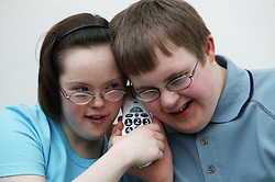 Teenage Downs Syndrome boy and girl listening on the telephone,