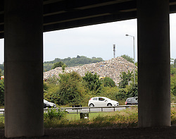 © Licensed to London News Pictures. 16/08/2015<br /> VIEW FROM CRITTALLS CORNER UNDER THE SIDCUP BY-PASS A20.<br /> A mountain of waste still towers over local residents in St Pauls Cray,Orpington,Kent.  TODAY (16.08.2015)<br /> The residents of Cornwall Drive are still having to put up with a stinking smell,rats and fires coming from the  Waste4fuel site which is based at the end of the cul-de-sac.   The waste pile which is 40ft high can be clearly seen from Sidcup by-pass A20 and Crittalls Corner roundabout and is the first landmark visitors to the area are greeted with.<br /> <br /> <br /> (Byline:Grant Falvey/LNP)