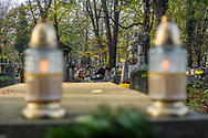 A woman puts candles and flowers on a grave of deceased loved ones in the Rakowicki cemetery in Krakow, Poland 2019.