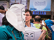 """09 JUNE 2013 - BANGKOK, THAILAND:  Members of the White Mask protest movement at an anti-government protest on the plaza in front of Central World in Bangkok. The White Mask protesters wear the Guy Fawkes mask popularized by the movie """"V for Vendetta"""" and the protest groups Anonymous and Occupy. Several hundred members of the White Mask movement gathered on the plaza in front of Central World, a large shopping complex at the Ratchaprasong Intersection in Bangkok, to protest against the government of Thai Prime Minister Yingluck Shinawatra. They say that her government is corrupt and is a """"puppet"""" of ousted (and exiled) former PM Thaksin Shinawatra. Thaksin is Yingluck's brother. She was elected in 2011 when her brother endorsed her.    PHOTO BY JACK KURTZ"""