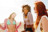 Three pretty young women enjoying a sunny beach day.