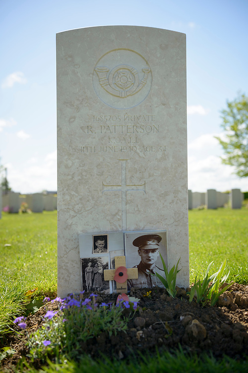 At the grave of Private R. Peterson, located at the Commonwealth Cemetery in Bayeux, France, photos and a message written on a cross have been left by his children.