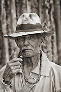Portrait of one of the Mountain Men at the Fort Bridger Rendezvous in southern Wyoming. The trapper is smoking a pipe and is wearing a sweat stained hat.