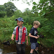 Two young boys pond dipping in a shallow stream, Danby, North York Moors, North Yorkshire, UK