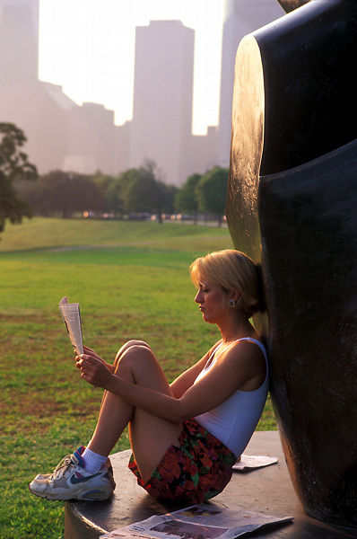 Stock photo of a woman in running attire sitting against a sculputre in Memorail Park reading a newspaper early in the morining