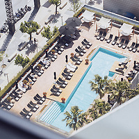 A swimming pool in the sun, where people are beginning to lounge.